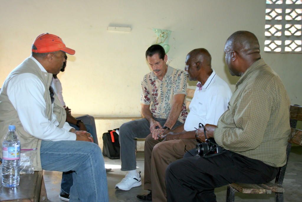 Tim Mastenbrook talking and praying with Pierre Delamar and Philton Telemarque at Limbe church with Sam Aikin and Ugochukwu Nwakanma